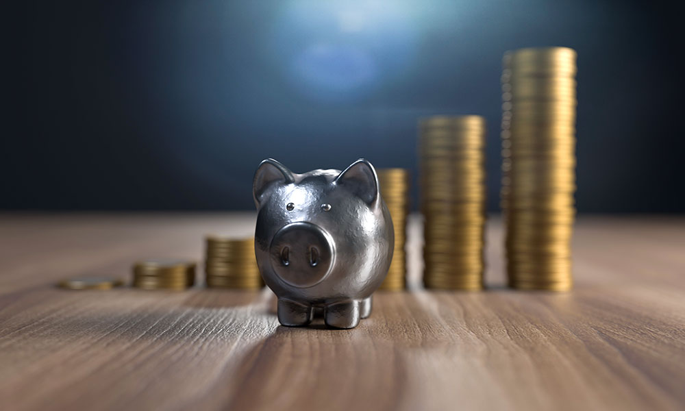 A Stainless Steel Pig on wood in front of stacks of increasing coins.